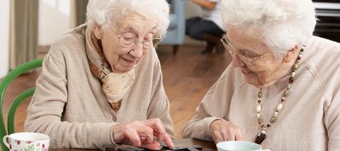 Two old ladies looking at something