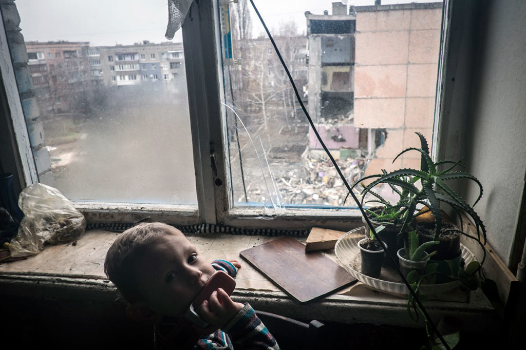 On 17 December, [NAME CHANGED] Nikita, 5, stand at a window in his family's apartment in a district in the city of Pervomaysk in Donetsk Oblast. Nikita, whose father was killed during shelling two months earlier while returning home from work, lives with his mother and grandmother. Visible across from the apartment is a building that was destroyed by recent shelling. Despite limited humanitarian access, UNICEF continues to provide aid in conflict-affected areas in Donetsk and Luhansk regions. By end December 2014 in Ukraine, at least 4,771 people had been killed and 10,360 had been wounded in the country's continuing conflict. More than 601,400 people have also been internally displaced, and an estimated 5.2 million people are living in conflict-affected areas. Additionally, over 593,600 others have sought refuge in neighbouring countries. The fighting has destroyed or disrupted essential infrastructure and basic services, leaving affected populations vulnerable and in need of urgent support. Despite renewed commitment to a September ceasefire, serious ceasefire violations continue to be reported daily; and although shelling has lessened in parts of the eastern oblasts of Donetsk and Luhansk– two of the five provinces most affected by the conflict – displacements continue to increase, and civilian safety remains a concern. Indiscriminate shelling and continued insecurity have placed conflict-affected people and humanitarian actors at risk, hampering the provision of humanitarian aid and disrupting access to essential medicines and health facilities, and to education. Children have been most affected by the conflict, with the most vulnerable forced to seek refuge underground in unsanitary conditions in crowded and freezing basements, cellars and bomb shelters – with little or no access to food water, sanitation or basic hygiene. In response to the continuing fighting, UNICEF is supporting health, nutrition, water, sanitation and hygiene (WASH), education