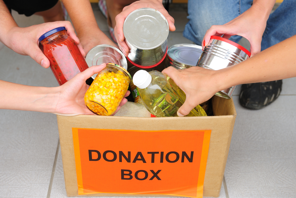 donation-box-hands-adding-cans